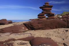 inukshuk made of red rocks - stock photo