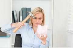 Stock Photo of determined woman wanting to destroy her piggy bank