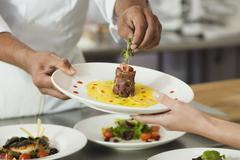 Chef putting garnish on plate of food Stock Photos