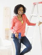 African woman holding cordless drill - stock photo