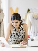 Mixed Race female sales clerk adding receipts Stock Photos
