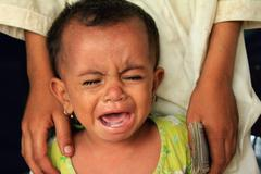 Refugee Baby Cries in Hunger Stock Photos