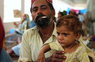 Refugee Man with Daughter in Pakistan Stock Photos
