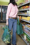 Asian woman shopping in health food store - stock photo