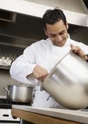 Hispanic male chef mixing batter Stock Photos