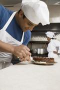 Hispanic male pastry chef decorating cake Stock Photos