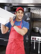 Hispanic male pizza maker holding box Stock Photos