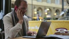 Young man with cellphone and modern laptop in cafe HD Stock Footage