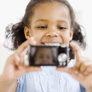 Mixed race girl taking self-portrait with digital camera - stock photo