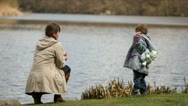 Stock Video Footage of Young mother and her daughter having fun near the river in the park.