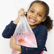 Sekarotuinen tyttö, jolla kultakala pussiin Kuvituskuvat