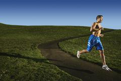 Bare chested Asian man jogging in park Stock Photos