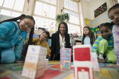 Multi-ethnic students in classroom with teacher Stock Photos