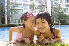 Asian sisters getting out of swimming pool Stock Photos