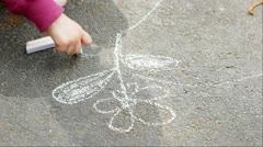 A child drawing a nice flower with sidewalk chalk. - stock footage