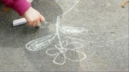 Stock Video Footage of A child drawing a nice flower with sidewalk chalk.
