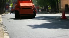 A steamroller rolls and compresses hot asphalt. - stock footage