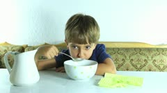 Boy eat granola with milk - stock footage