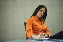 Latin American businesswoman writing in office Stock Photos