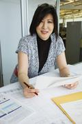 Asian American businesswoman working in office - stock photo