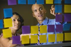 Multi-ethnic business people reviewing sticky notes Stock Photos