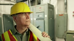 electrical engineer with plans smiles at camera - stock footage