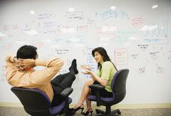 Multi-ethnic business people brainstorming on whiteboard Stock Photos