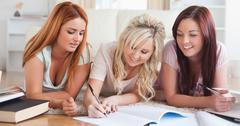Charming women lying on the floor learning - stock photo
