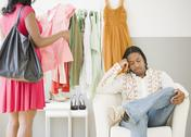 African man bored while woman shops Stock Photos