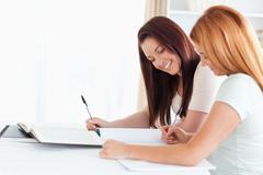Joyful Women sitting at a table learning - stock photo