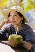 Japanese woman next to coconut - stock photo