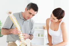 Chiropractor and patient looking at a model of a spine - stock photo