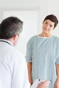 Cute Woman in hospital gown talking to her doctor - stock photo