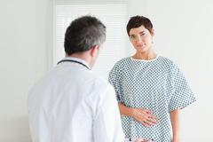 Brunette Woman in hospital gown talking to her doctor - stock photo