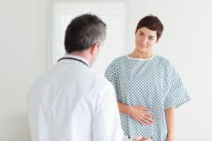 Young Woman in hospital gown talking to her doctor - stock photo