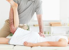 Chiropractor is stretching a woman's leg - stock photo