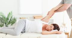 Chiropractor stretching woman's arm Stock Photos