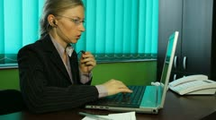 Businesswoman working at her desk, busy, office, callphone, hands-free Stock Footage