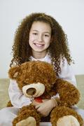 Mixed race girl in nightgown with teddy bear Stock Photos