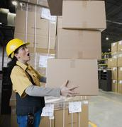 Hispanic woman carrying stack of boxes Stock Photos