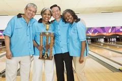 Bowling team with trophy in bowling alley - stock photo