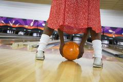 African woman playfully rolling bowling ball in bowling alley Stock Photos