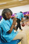 African woman rubbing aching wrist in bowling alley Stock Photos