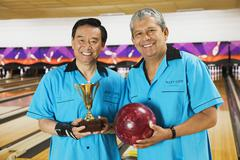 Multi-ethnic teammates holding bowling ball and trophy Stock Photos