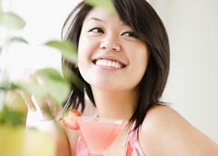 Asian woman drinking pink martini Stock Photos