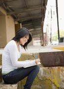 Asian woman writing and sitting on loading dock Stock Photos