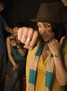 Mixed race woman punching air in nightclub Stock Photos
