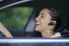 Hispanic woman driving with hands-free cell phone device Stock Photos