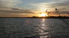 Boat passes by sunset at lake during summer. Stock Footage