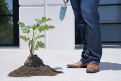Asian man standing near pile of soil and plant Stock Photos
